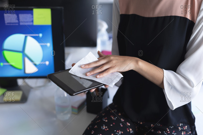 Mid section of woman cleaning digital tablet with tissue at modern office.