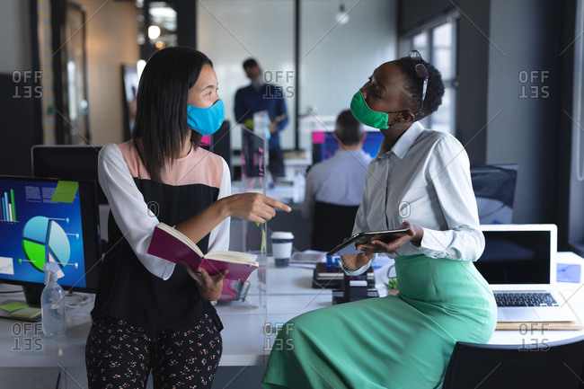 Asian woman with book and African American woman with digital tablet talking to each other at modern office.