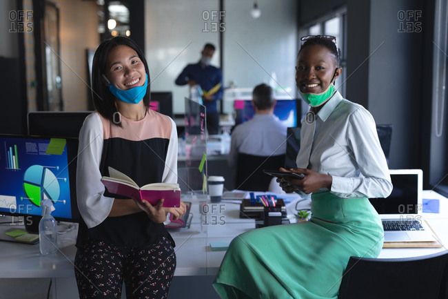 Portrait of Asian woman with book and African American woman with digital tablet at modern office.