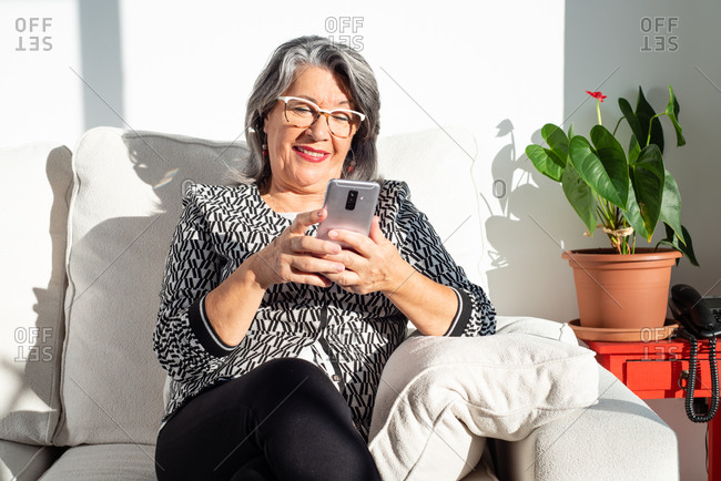 Smiling mature female in classic outfit and eyeglasses browsing modern mobile phone while sitting with legs crossed on comfy sofa