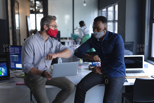 Diverse male colleagues wearing face masks greeting each other by touching elbows while at modern office.