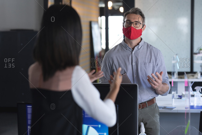 Caucasian man and woman wearing face masks talking to each other at modern office.