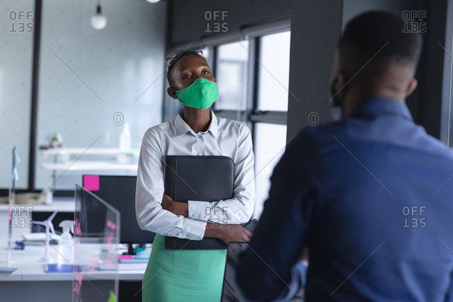 African American woman wearing face mask talking to her office colleague at modern office.