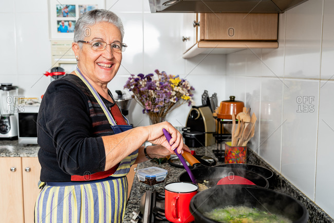 Happy mature woman frying red onion in hot pan with oil while preparing traditional catalan fish dish in home kitchen looking at camera