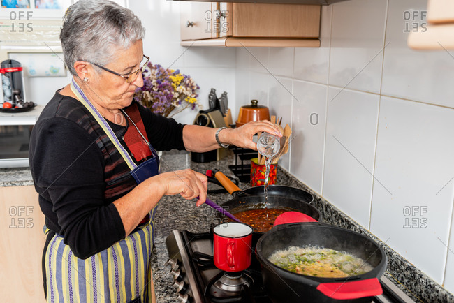 Side view of senior housewife pouring water into frying pan with mixed ingredients while preparing traditional catalan fish dish in home kitchen