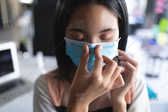 Close up of Asian woman wearing face mask touching her nose at modern office.