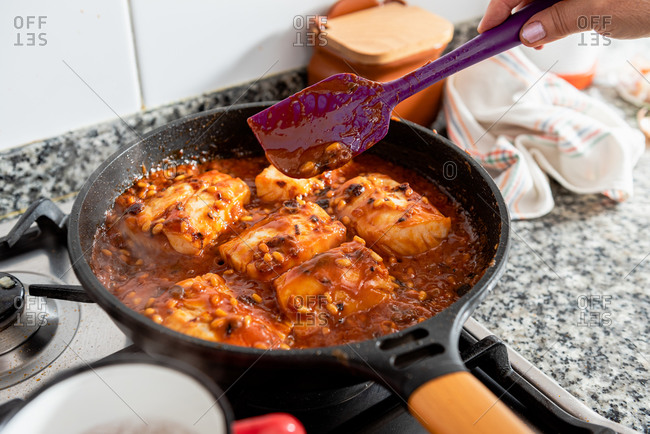 Closeup of frying pan with cod steaks and aromatic spicy red sauce