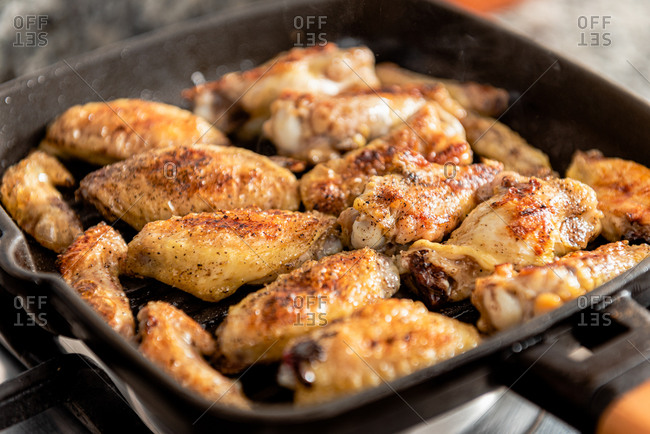 Closeup of hot freshly roasted chicken with appetizing crust in frying pan in kitchen