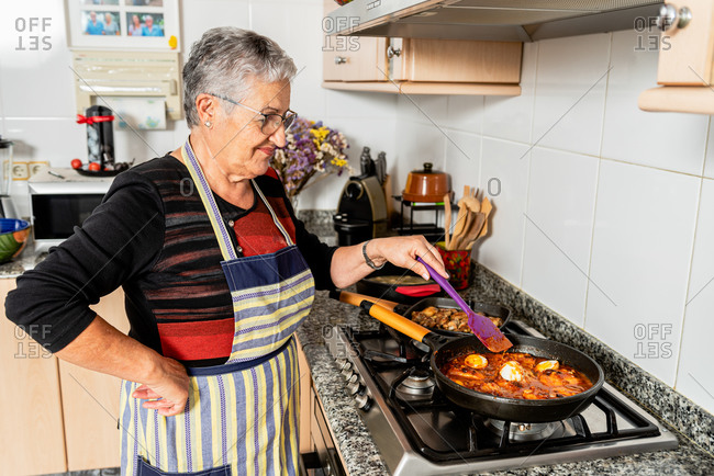 Side view of senior housewife with spatula stirring sauce with fish steaks in frying pan while preparing typical catalan cod dish in kitchen