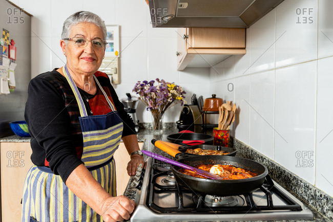 Senior housewife cooking fish steaks in frying pan while preparing typical catalan cod dish in kitchen looking at camera
