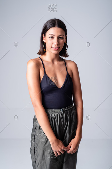 Beautiful smiling female wearing black low neckline top standing against white background in studio and looking at camera happily