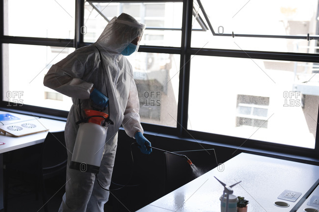 Health worker wearing protective clothes cleaning office using disinfectant.