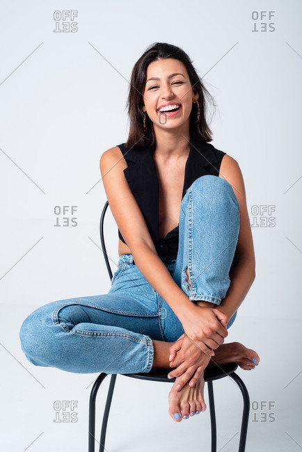 Full body delighted slim female model in tight jeans and top sitting on chair in light studio