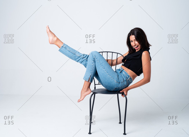 Side view full body delighted slim female model in tight jeans and top sitting with leg raised on chair in light studio