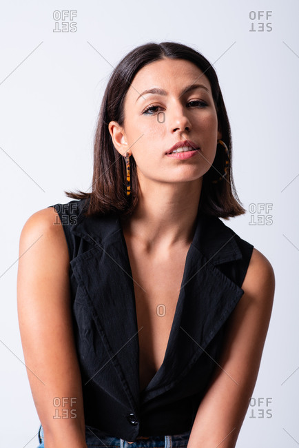 Beautiful female wearing black low neckline top standing against white background in studio and looking at camera