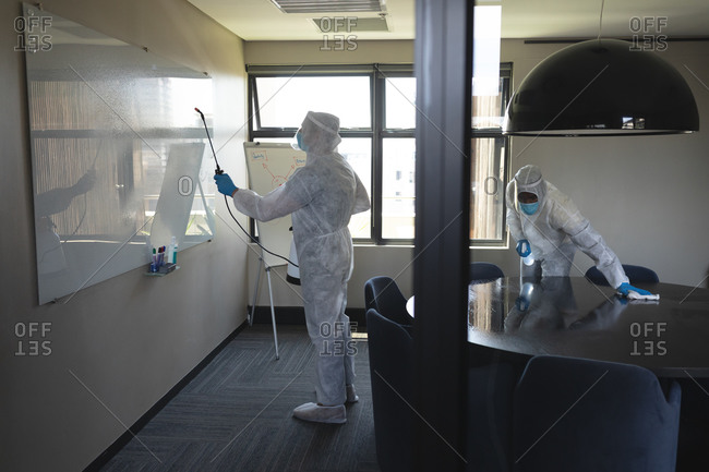 Team of health workers wearing protective clothes cleaning office using disinfectant.