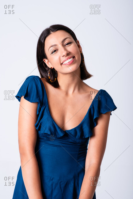 Attractive young brunette wearing low neckline blue dress standing against white wall in light studio and looking at camera with charming smile