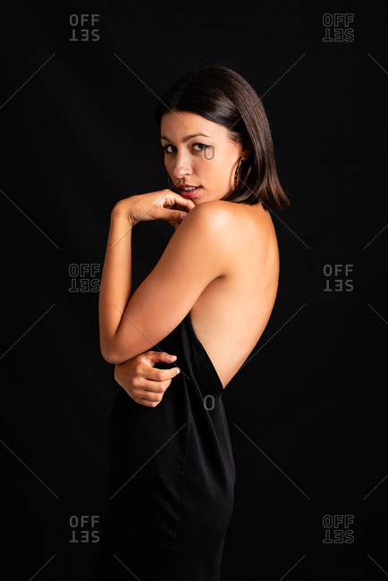 Beautiful female wearing black dress standing against black background in studio and looking at camera
