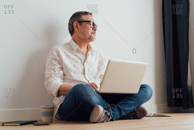 Contemplative senior male sitting with legs crossed on parquet with netbook on laps