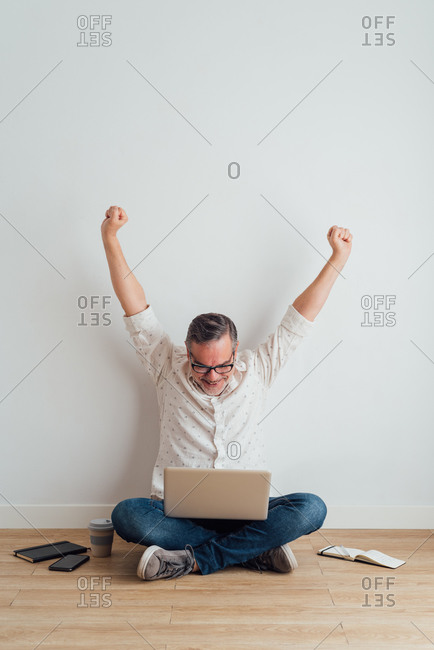 Full body delighted mature male wearing casual clothes sitting on floor with contemporary laptop on laps and raising arms in triumph