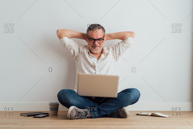 Full body delighted pleased mature male wearing casual clothes sitting on floor with contemporary laptop on laps