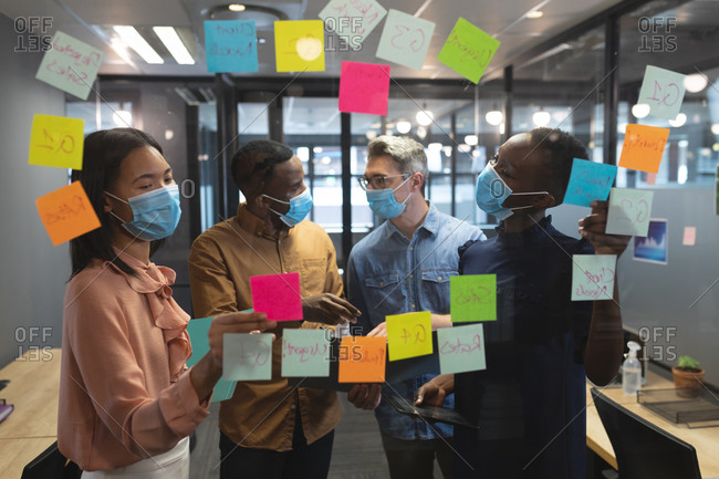 Diverse office colleagues wearing face masks discussing over memo notes on glass board at modern office.