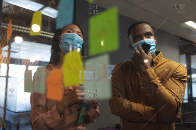 African American man and Asian woman wearing face masks discussing over memo notes on glass board at modern office.