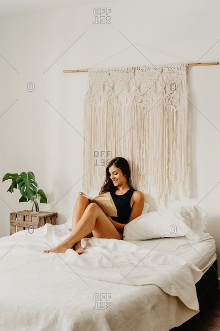 Positive young female in underwear sitting on cozy bed and reading book while spending weekend morning in light bedroom with boho decoration