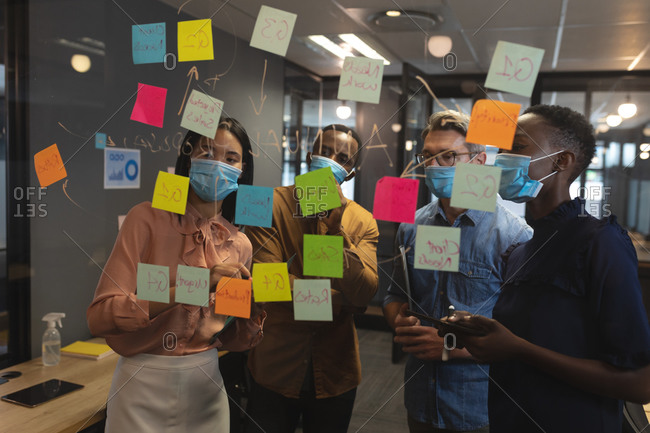 Diverse office colleagues wearing face masks brainstorming in office. discussing over memo notes on glass board at modern office.