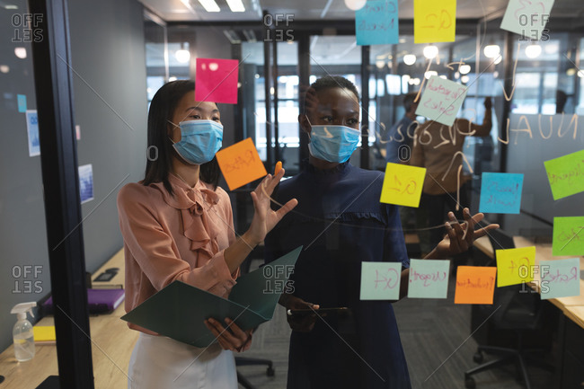 Diverse female colleagues wearing face masks brainstorming in office. discussing over memo notes on glass wall at modern office.