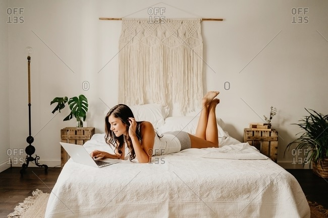 Cheerful millennial female in nightwear lying on bed and surfing internet on laptop while spending weekend morning in cozy bedroom with minimalist interior