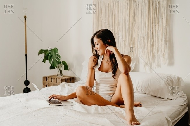 Delighted young female in sleepwear laughing happily while sitting on bed and browsing laptop after awakening in light bedroom in morning