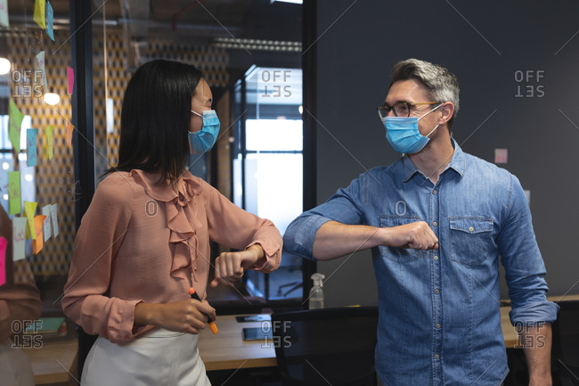 Caucasian man and Asian woman wearing face masks greeting each other by touching elbows at modern office.