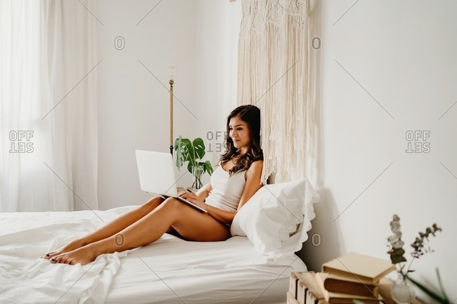 Delighted young female in sleepwear sitting on bed and browsing laptop after awakening in light bedroom in morning