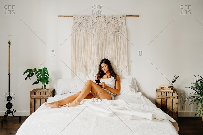 Young smiling female in shirt and panties using modern smartphone while sitting on cozy bed in light bedroom