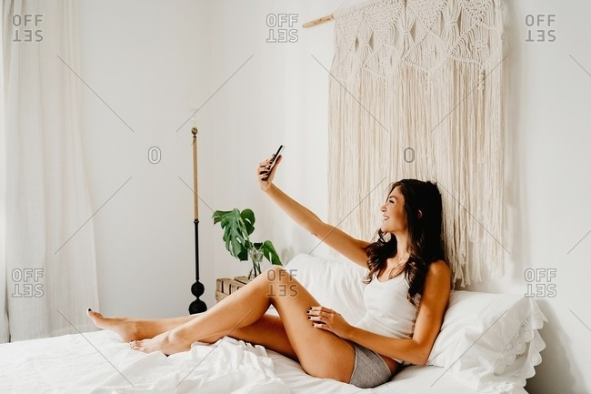 Side view of cheerful young teen female in sleepwear sitting on bed and taking selfie on smartphone while enjoying morning at home