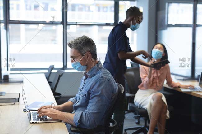 Caucasian man wearing face mask using laptop while African American woman and Asian woman wearing face masks discussing over digital tablet at modern office.