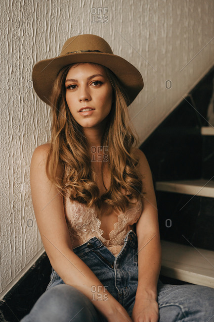 Calm female wearing hat and stylish jeans relaxing on wooden steps in modern house while looking at camera