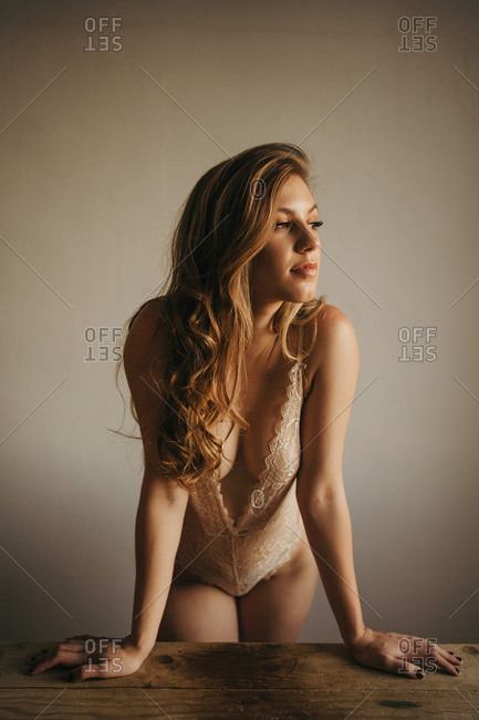 Young sensual pondering female in trendy underwear standing leaned with hands on table while looking away