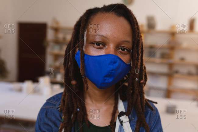 Portrait of mixed race woman wearing face mask at pottery studio.