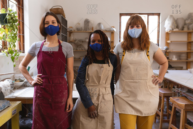 Two caucasian and one mixed race female potters in face masks working in pottery studio.