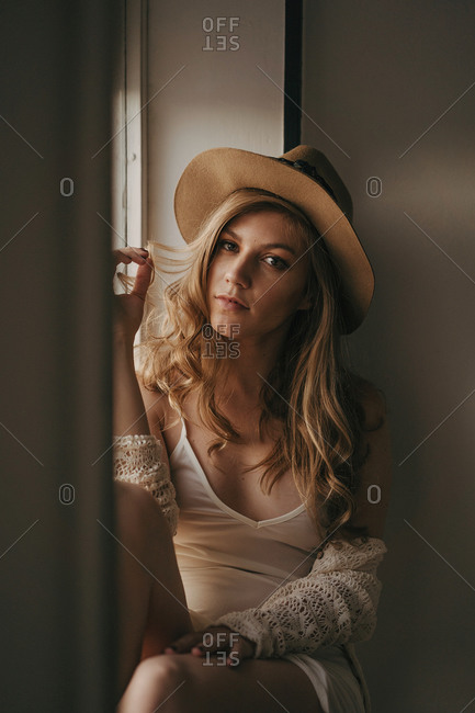 Young contemplative female in trendy wear and straw hat looking at camera near window at home
