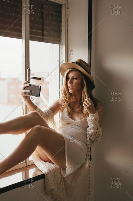 Young sensual female in trendy outfit and straw hat taking selfie on smartphone while sitting on windowsill