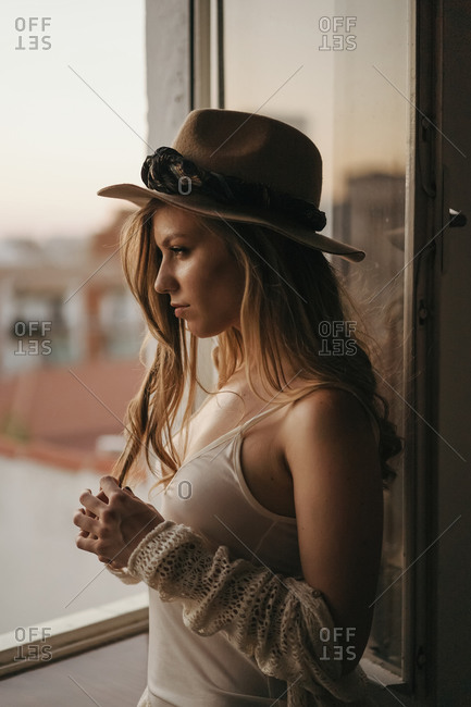 Young seductive female in stylish apparel and straw hat standing looking away on windows in apartment