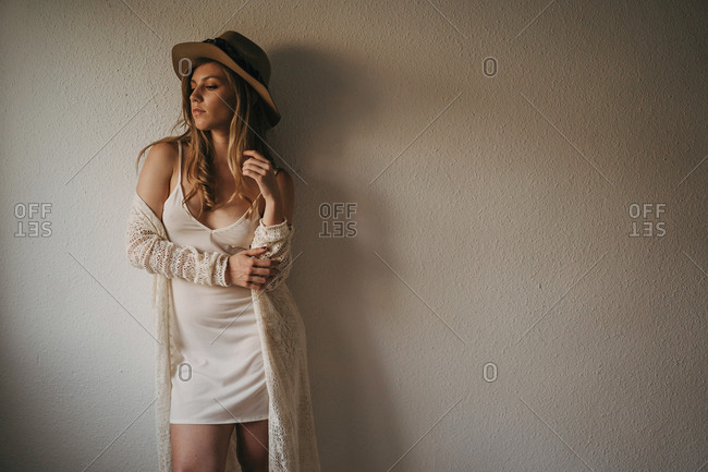 Young dreamy female in trendy wear and straw hat looking away near wall in house