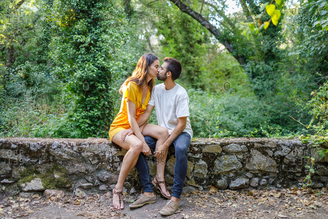 Full body of young stylish couple in casual clothes kissing while sitting on stone border against lush green trees in summer park