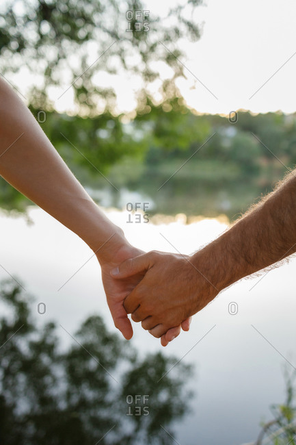 Crop anonymous romantic couple holding hands gently while spending time together in abundant lush nature on sunny weather