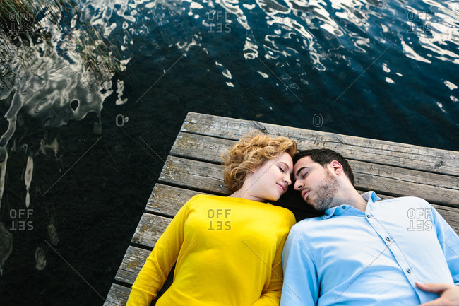 From above of couple lying on wooden quay near lake and tenderly looking at each other