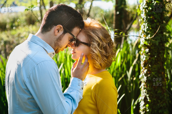 Side view of calm man tenderly touching cheek of woman while standing face to face