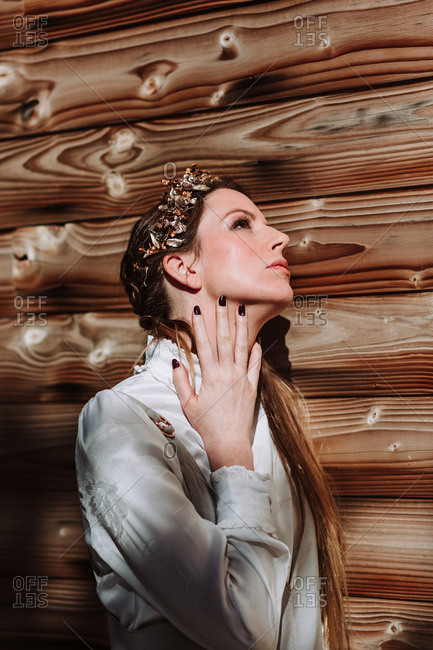 Side view attractive serene female in white blouse and wreath touching neck gently while standing near log house wall and looking up